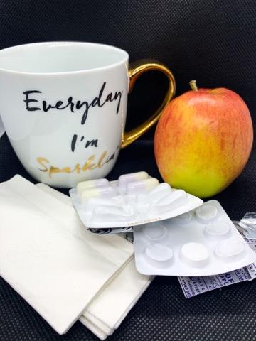Flu stuff, mug, apple, medication, tissues